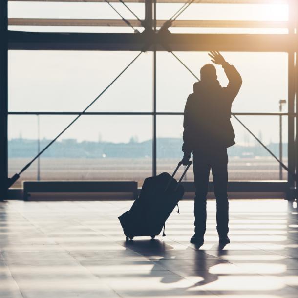 Silhouetted person at the airport with luggage waving goodbye